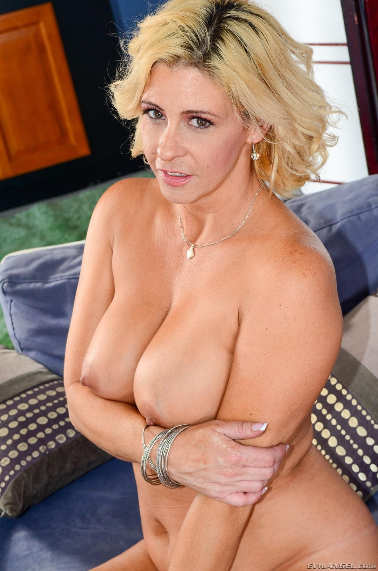 Beautiful blonde milf jane doux in black stockings posing on bed